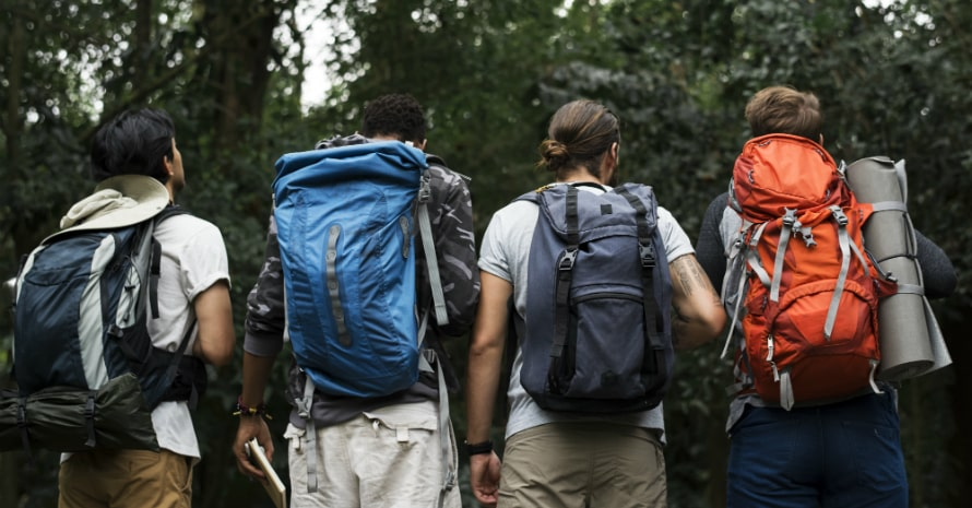 four friends with the backpacks in the wood