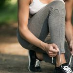 a girl sat down to tie shoelaces while jogging
