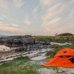 Orange-camping-tent-at-the-water