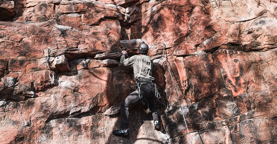 man in harnesses climbs